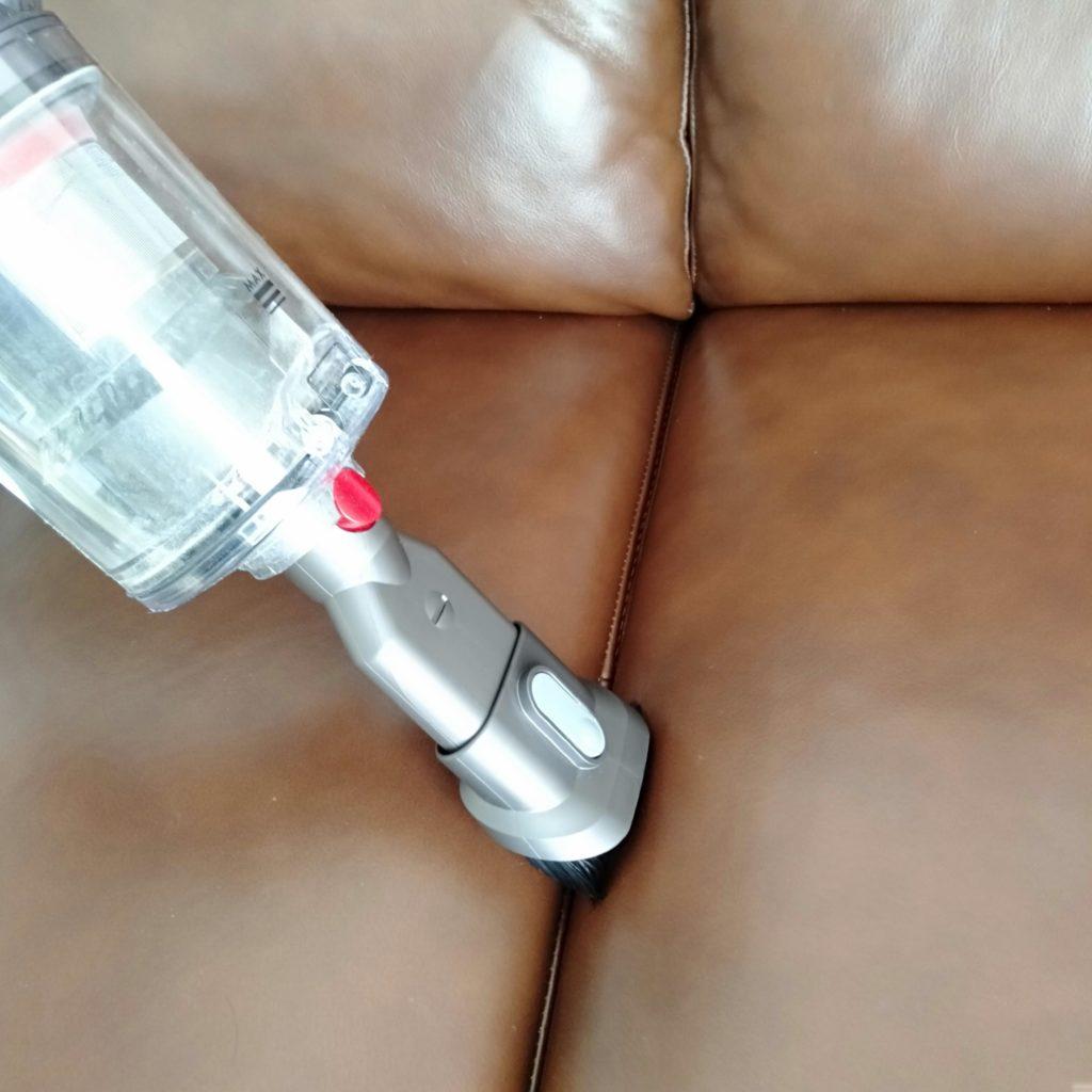 ソファの隙間を掃除機している画像
